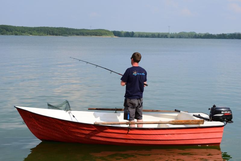 Angler steht auf dem Boot mit der Angelrute in der Hand