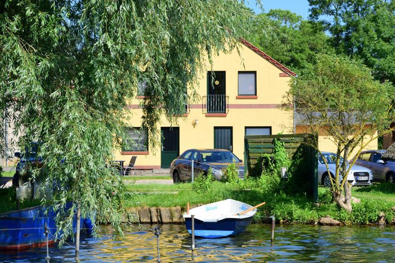 Boot im Wasser, dahinter Ferienwohnungen und einige Autos